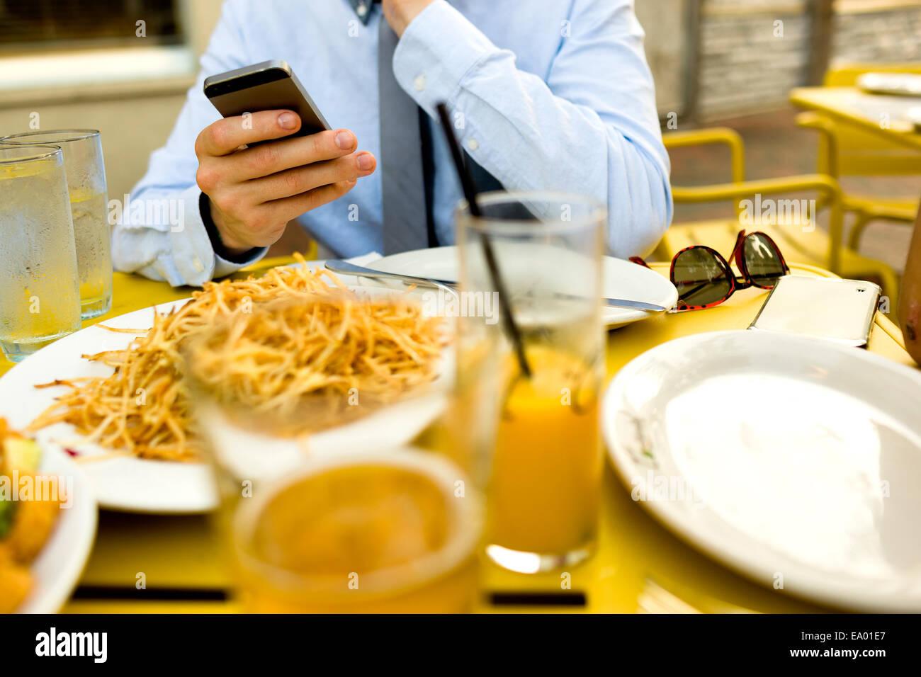 Ritagliato colpo di giovane uomo texting sullo smartphone al cafè sul marciapiede Immagini Stock