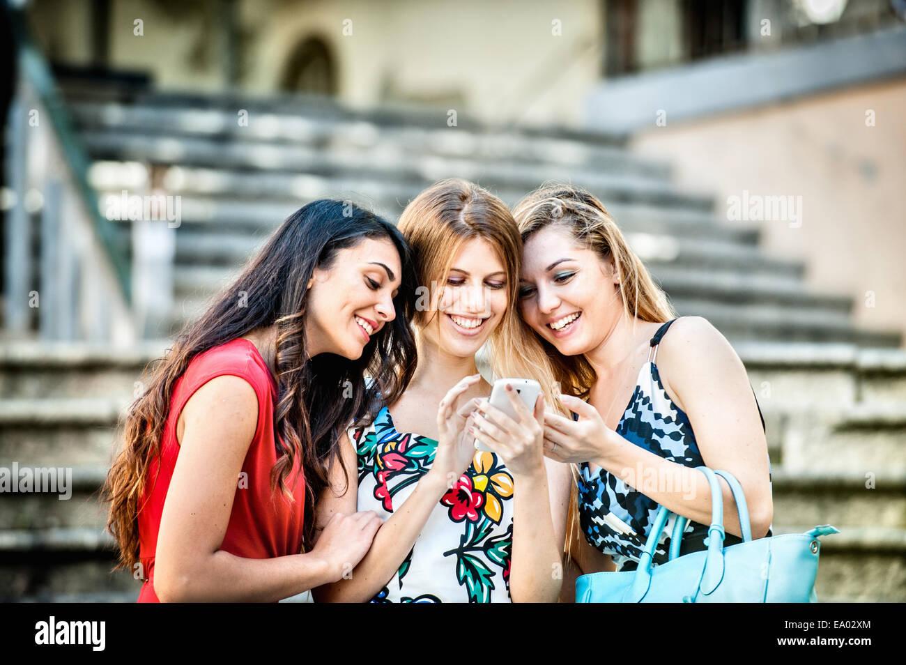 Tre giovani alla moda donna guardando smartphone, Cagliari, Sardegna, Italia Immagini Stock