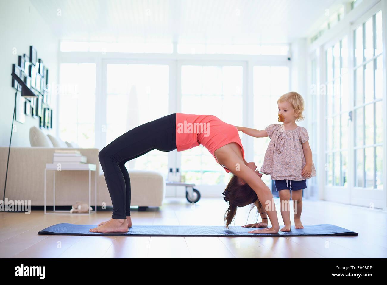 Metà adulto madre la pratica dello yoga con curiosi toddler figlia Immagini Stock