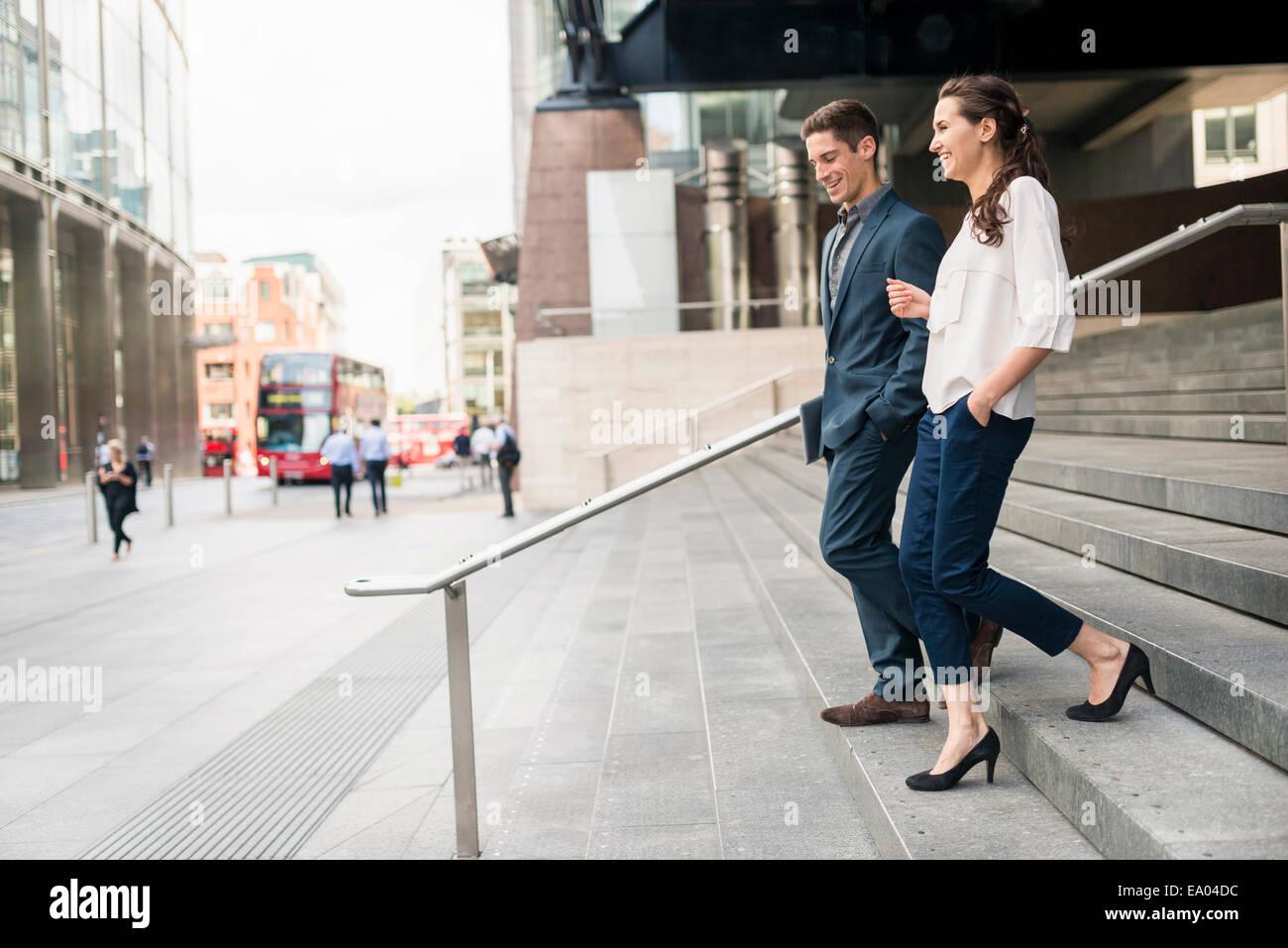 Vista posteriore del giovane imprenditore e la donna in chat mentre scendendo le scale, London, Regno Unito Immagini Stock