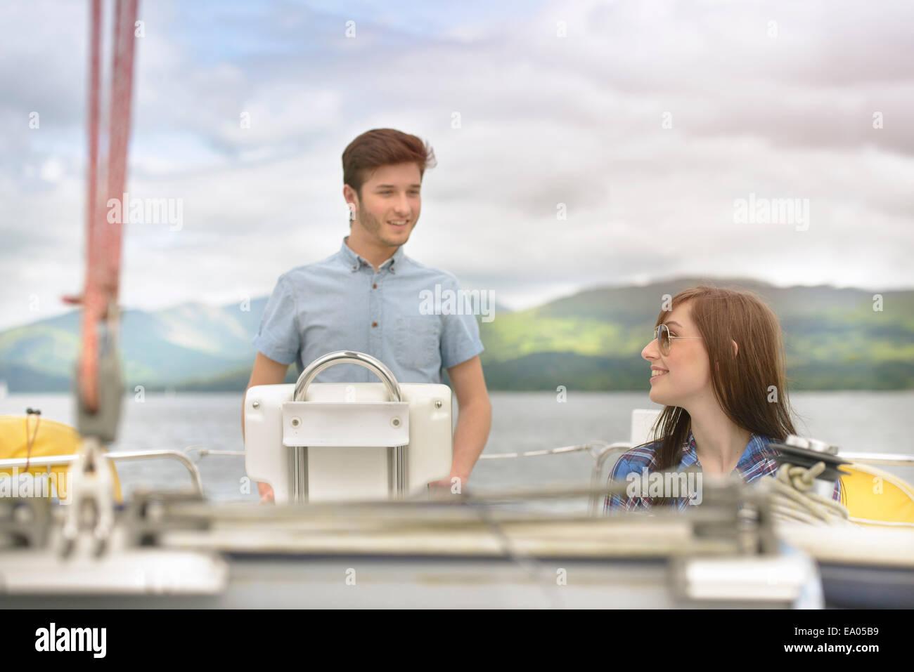 Coppia giovane vela su yacht sopra il lago Immagini Stock
