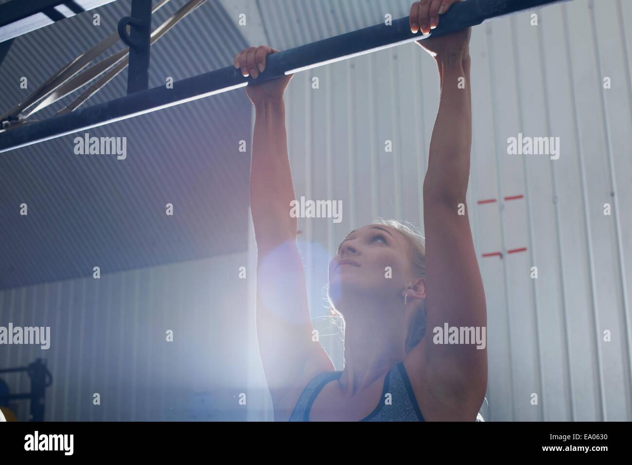 Donna facendo tirare ups in palestra Foto Stock