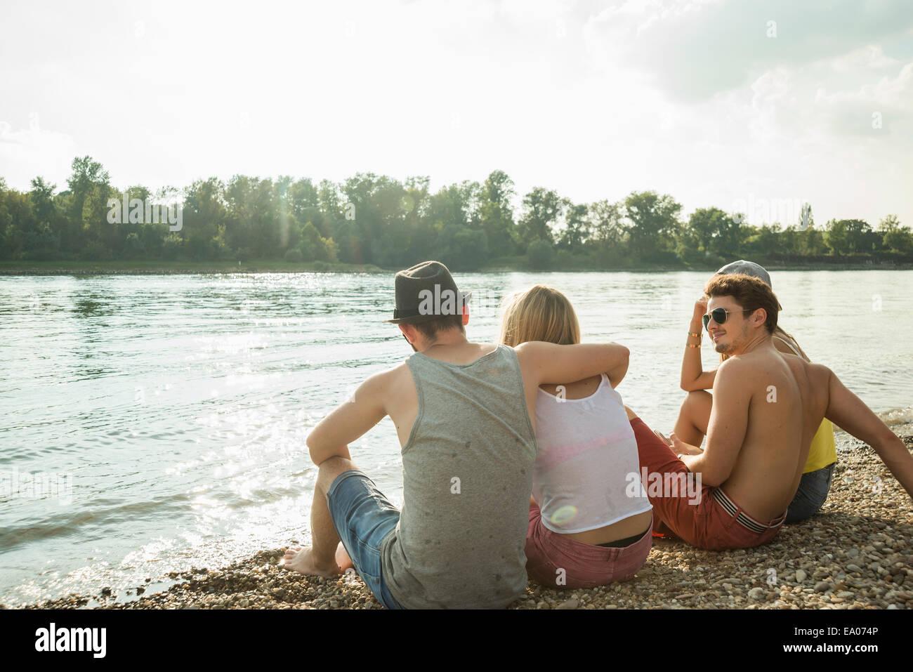 Quattro giovani amici seduti sul lungolago Immagini Stock