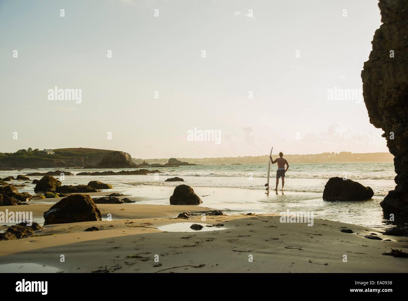 Uomo maturo permanente al bordo delle acque tenendo tavola da surf Immagini Stock
