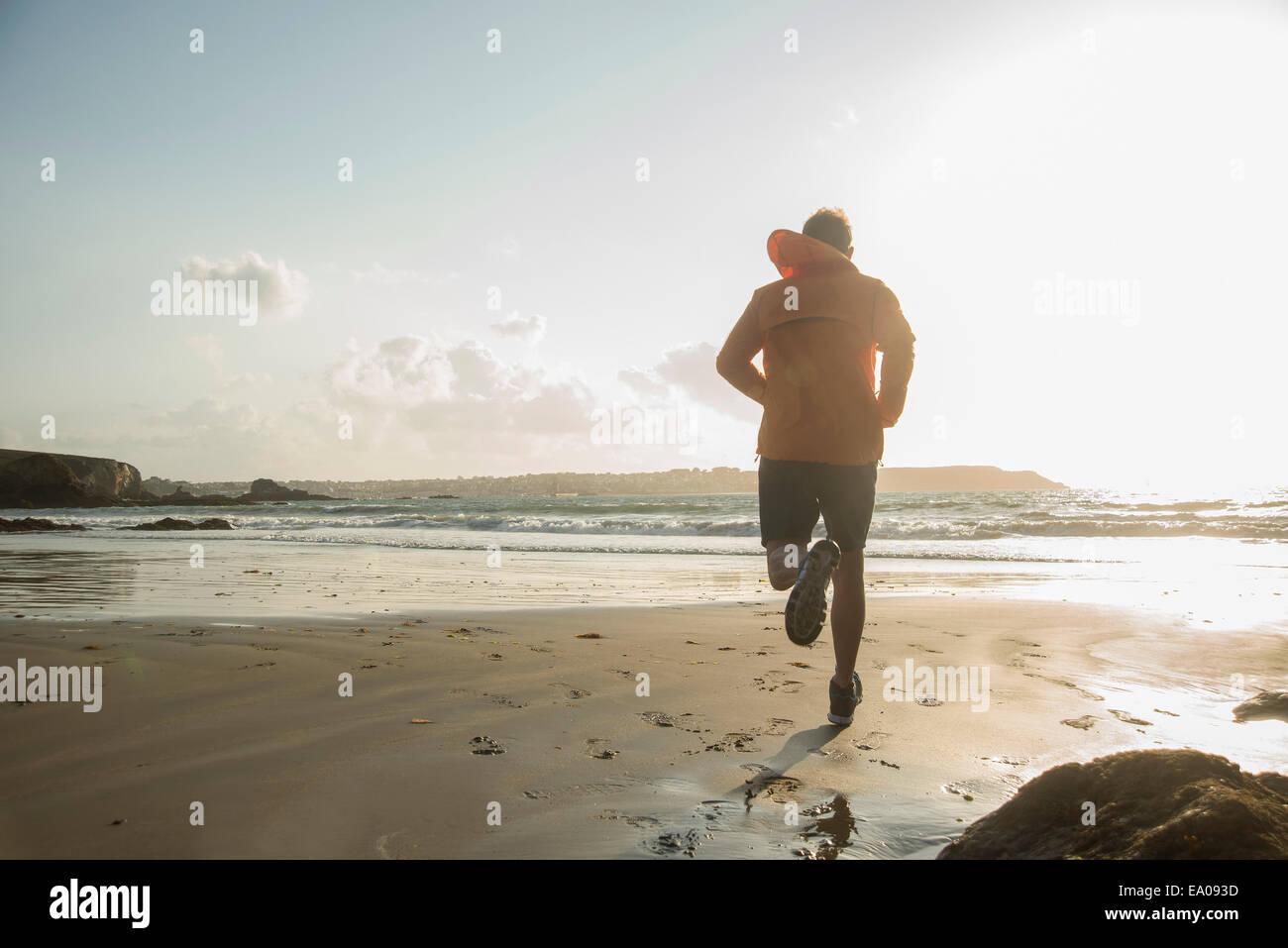 Uomo maturo in esecuzione sulla sabbia, lungo la linea costiera Immagini Stock