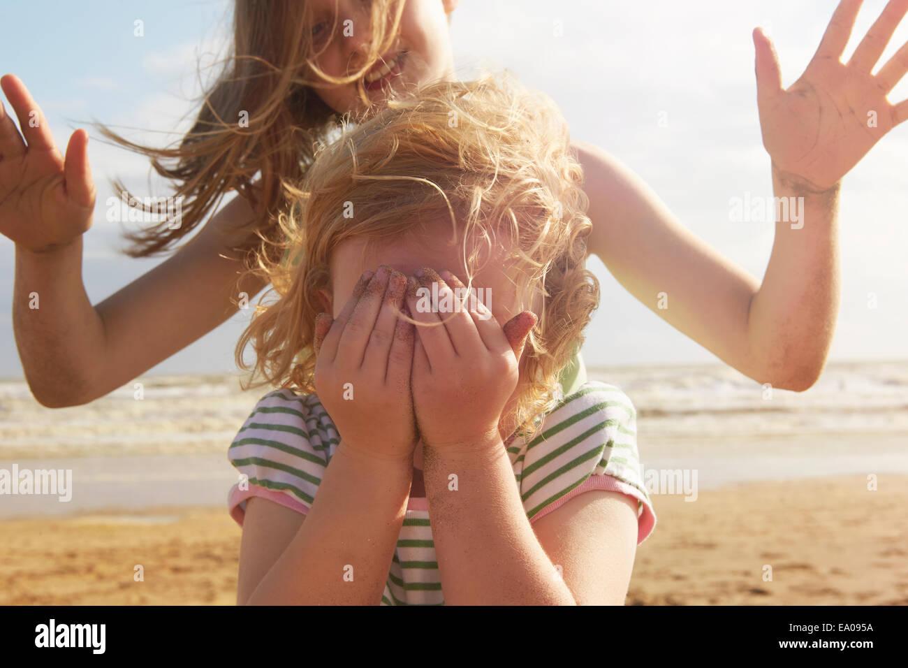 Ragazza che copre gli occhi di fronte a suor sulla spiaggia, Camber Sands, Kent, Regno Unito Immagini Stock