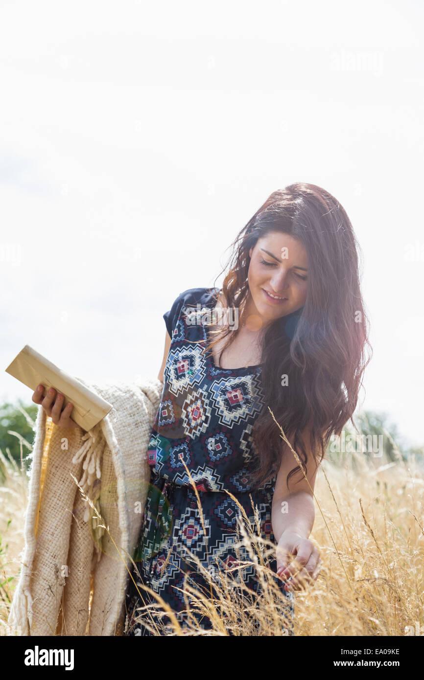 Giovane donna in campo con una coperta e prenota Immagini Stock