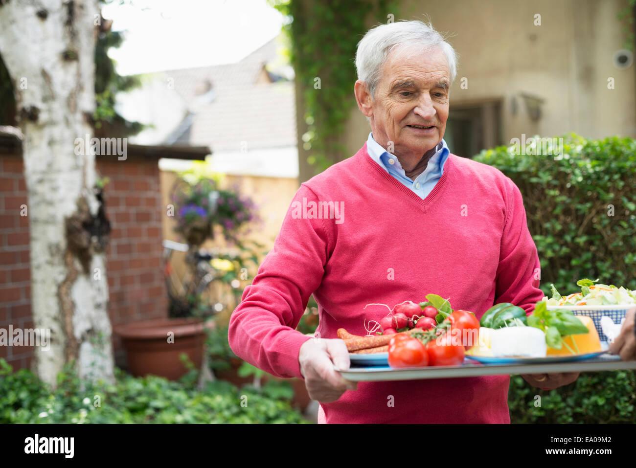 Senior uomo che porta il vassoio del cibo fresco Immagini Stock