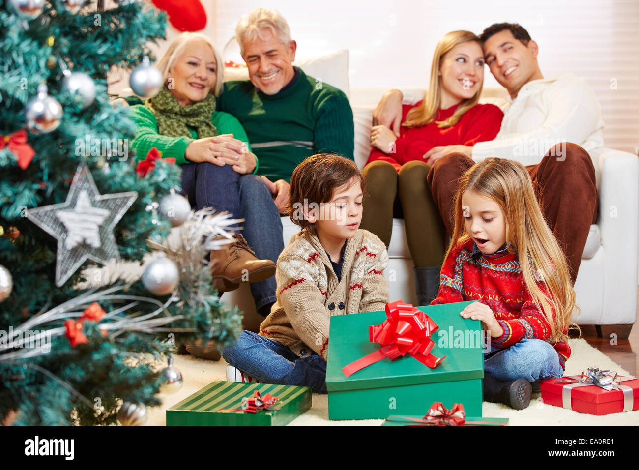 Apertura Regali Di Natale.Dei Bambini Felici Apertura Dei Regali A Natale Mentre I Genitori E I Nonni Stanno A Guardare Foto Stock Alamy