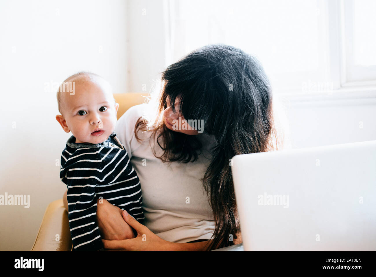 Madre utilizzando laptop con figlio al giro Immagini Stock
