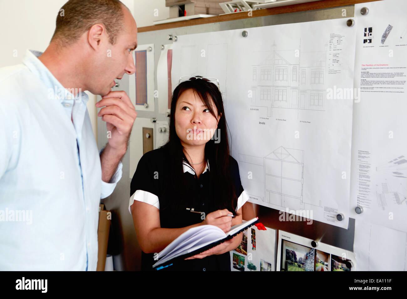 Maschio e femmina architetti guardando blueprint in office Immagini Stock