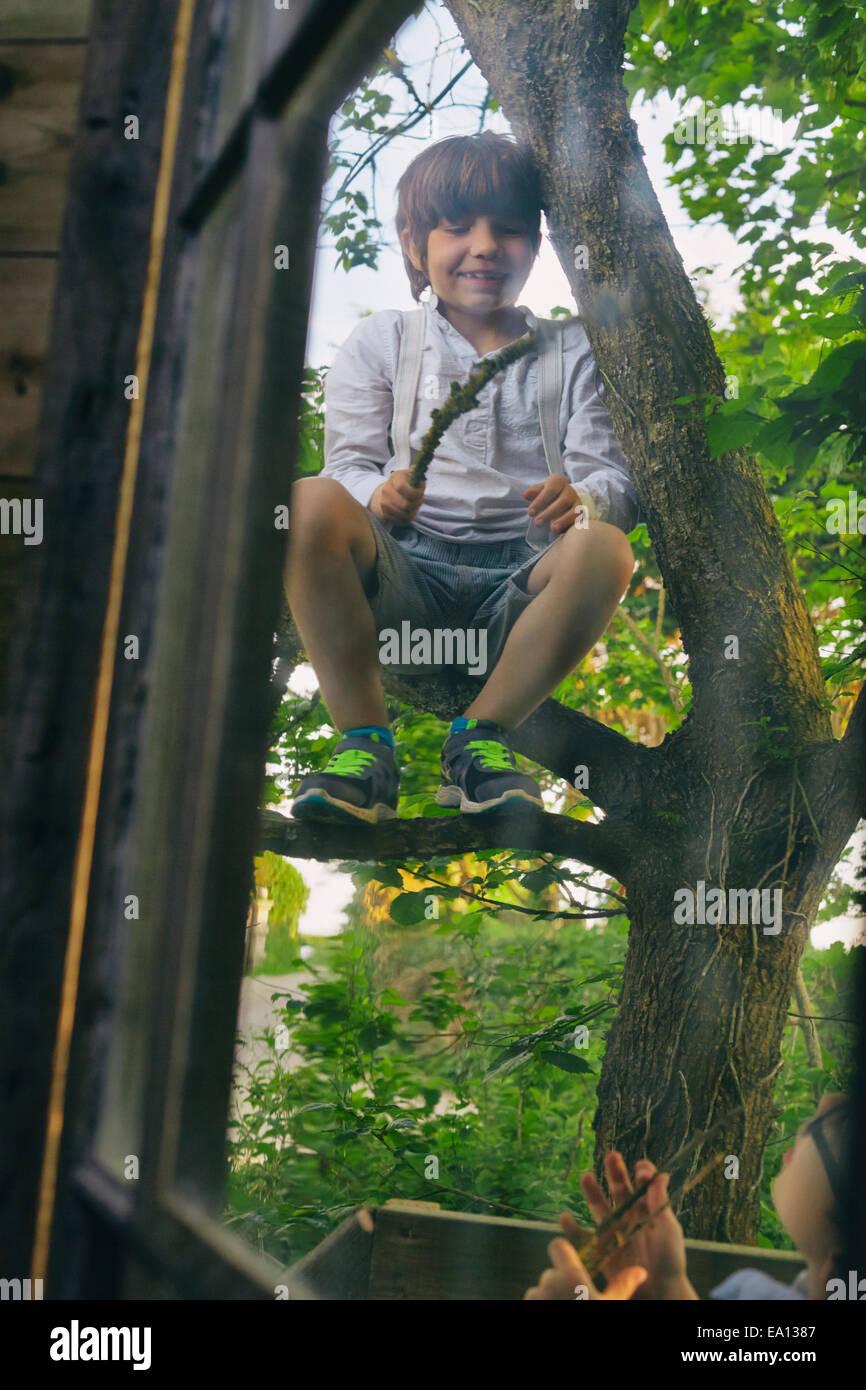 Due ragazzi giocare nella struttura ad albero al di fuori della finestra capanna Immagini Stock