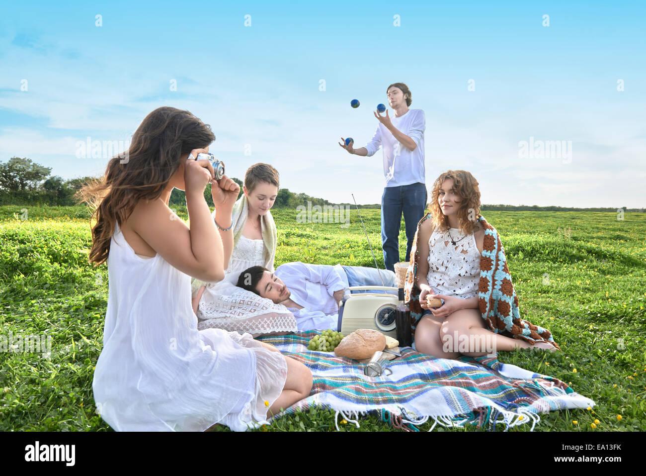 Un gruppo di giovani amici adulti aventi un picnic nel campo Immagini Stock