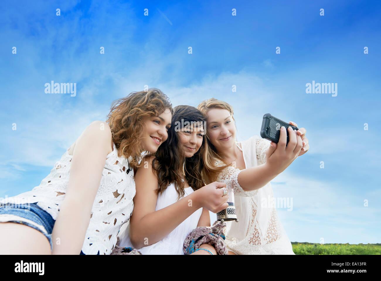 Tre giovani donne in campo in posa per selfie sullo smartphone Immagini Stock