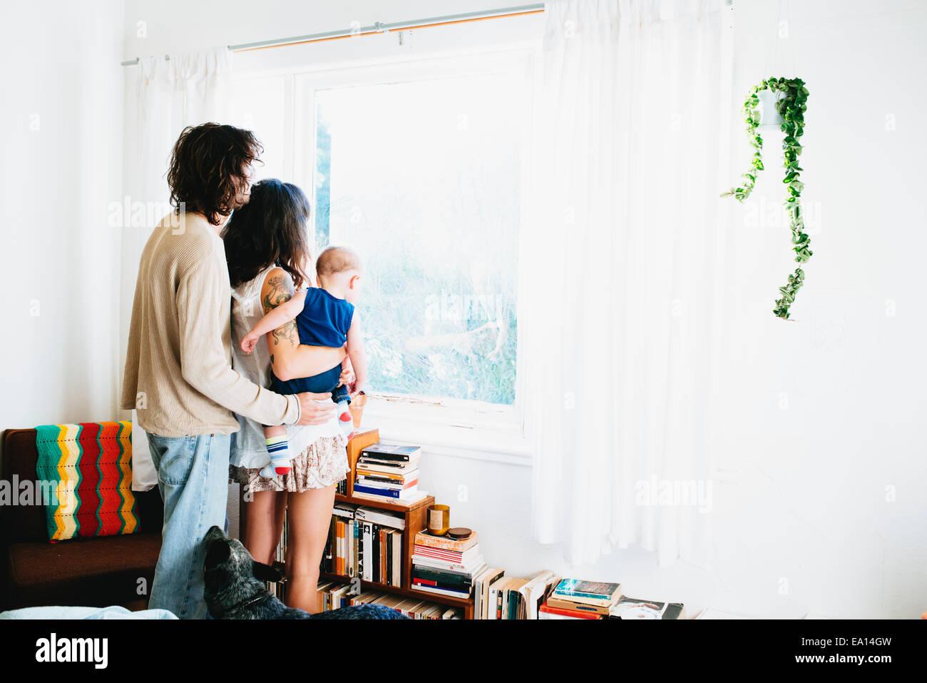 Famiglia guardando fuori della finestra Immagini Stock