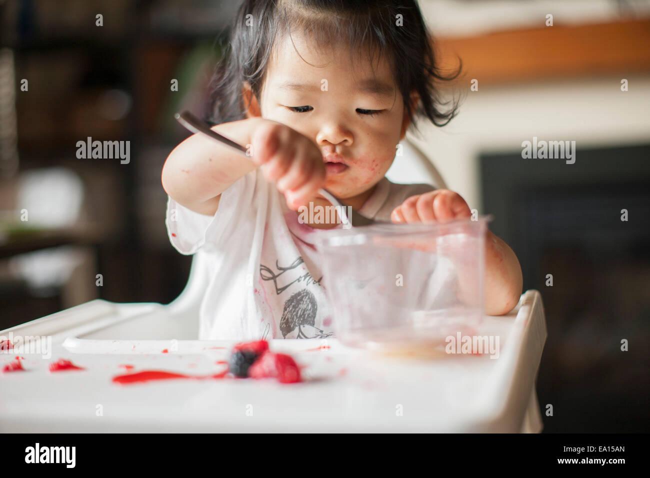 Un anno di età Baby girl mangiare la frutta nel seggiolone Immagini Stock
