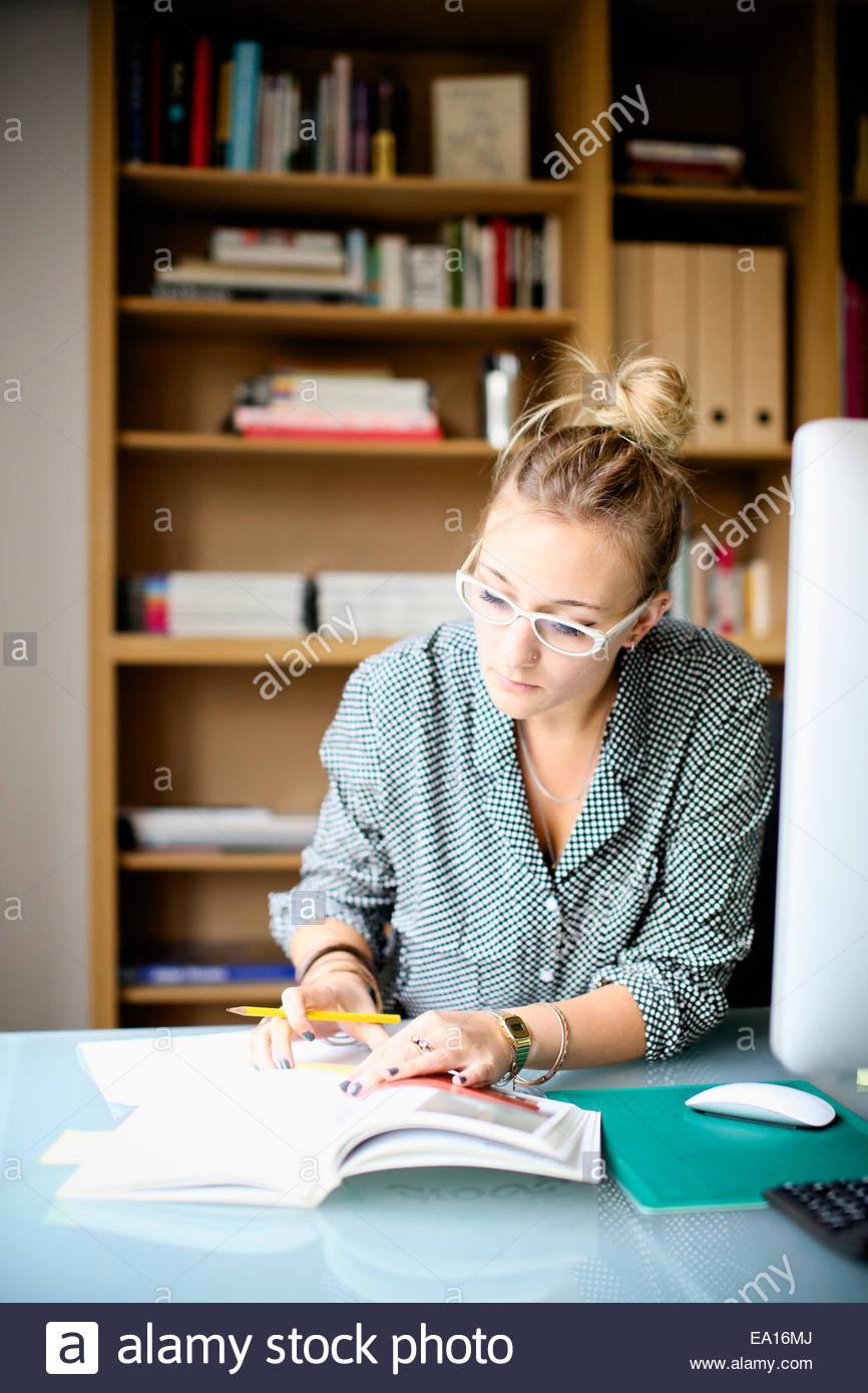La donna la lettura e la scrittura in un libro Immagini Stock