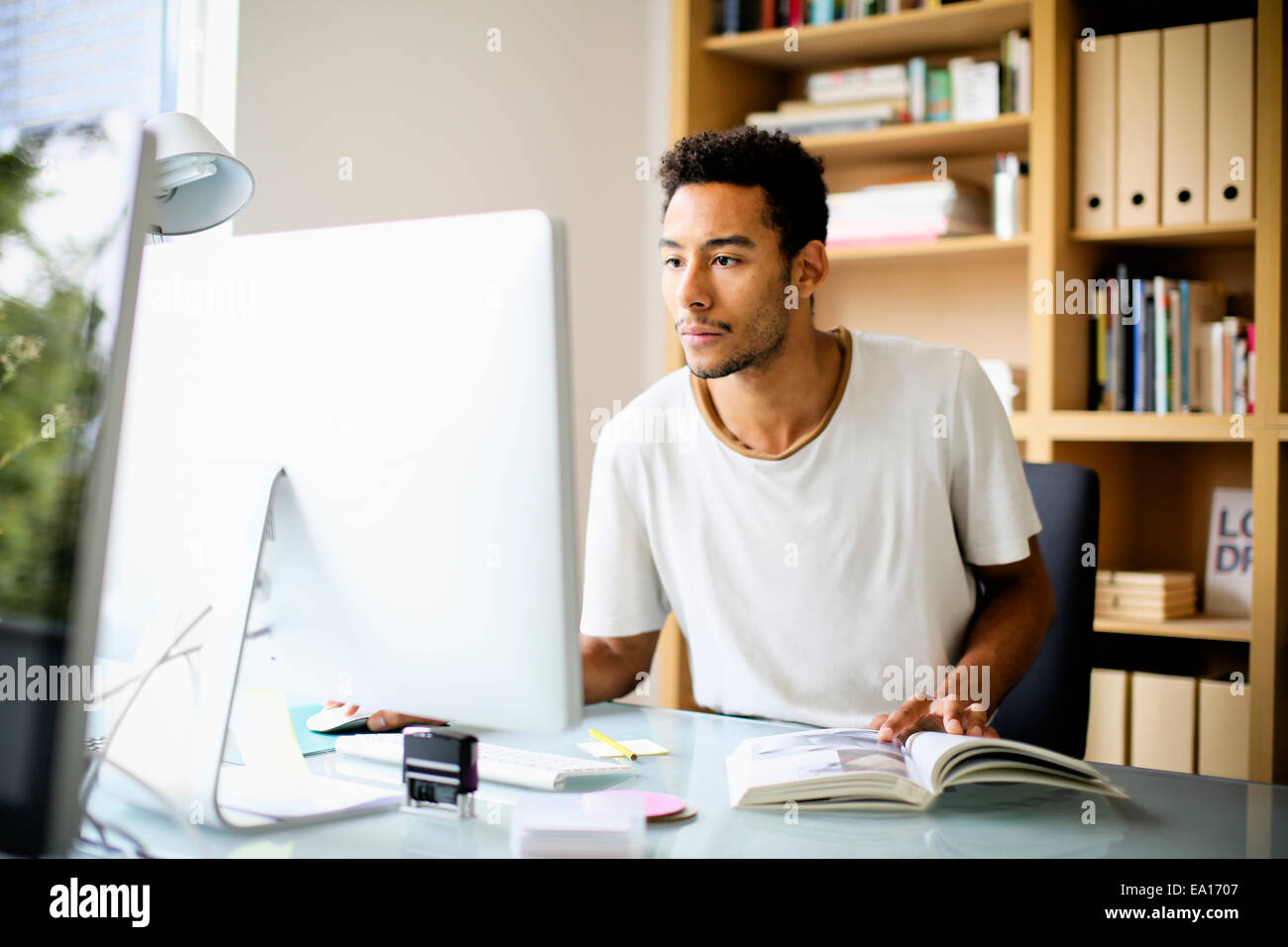 Graphic designer utilizzando computer sul posto di lavoro Immagini Stock