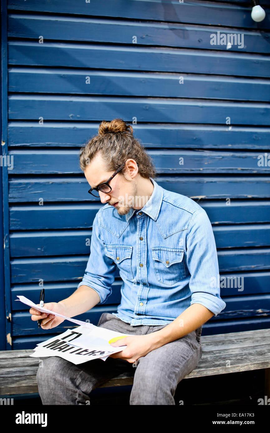 Giovane uomo guardando a stampe di disegni al di fuori Immagini Stock