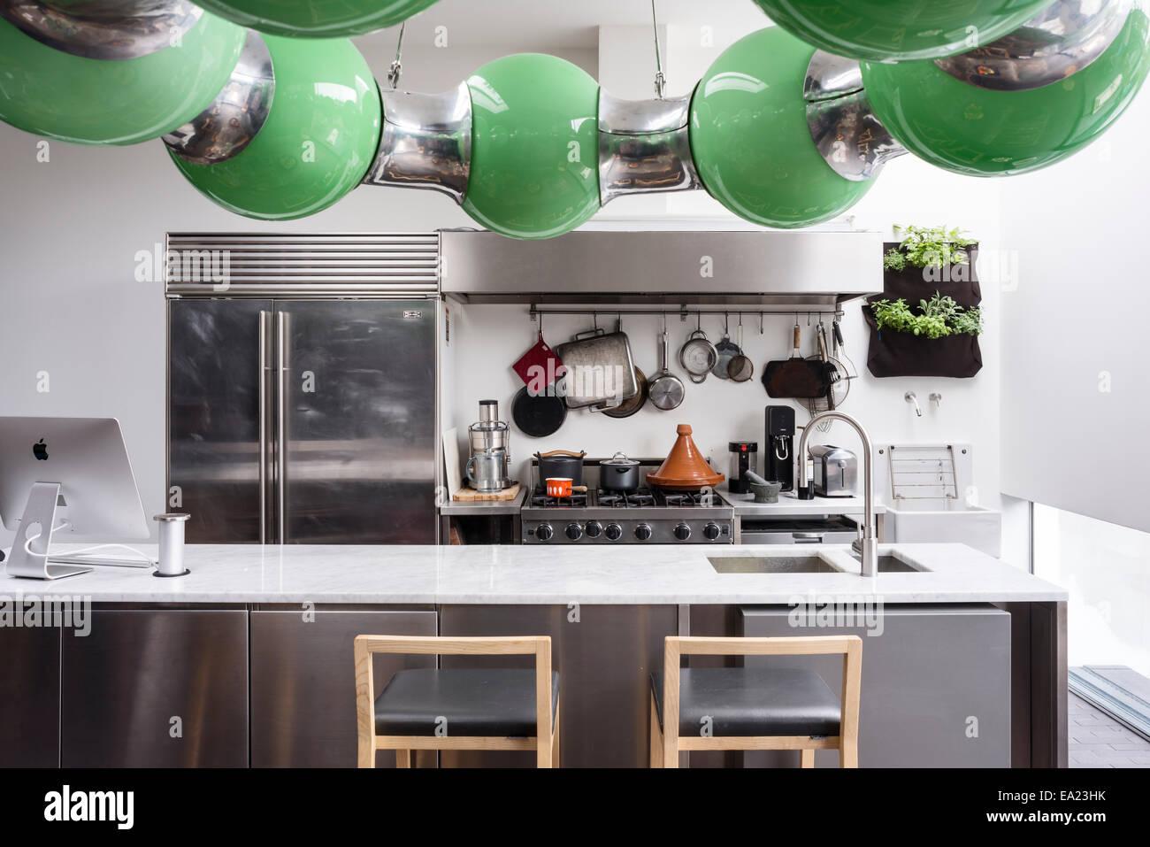 Moderna cucina con piano di lavoro di marmo e sgabelli bar foto