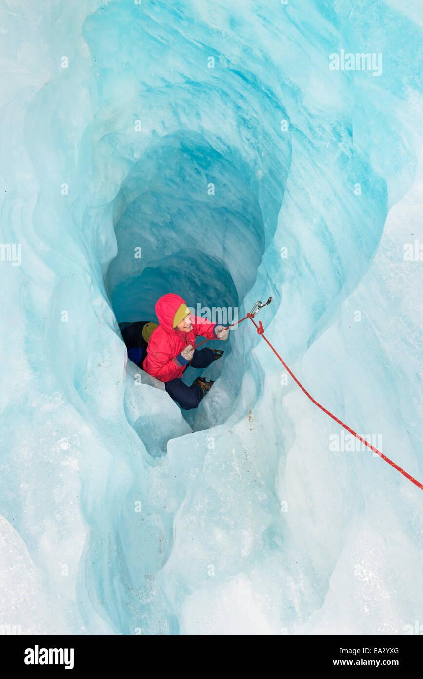 Rocciatore il movimento verso la grotta di ghiaccio, Fox Glacier, South Island, in Nuova Zelanda, Pacific Immagini Stock