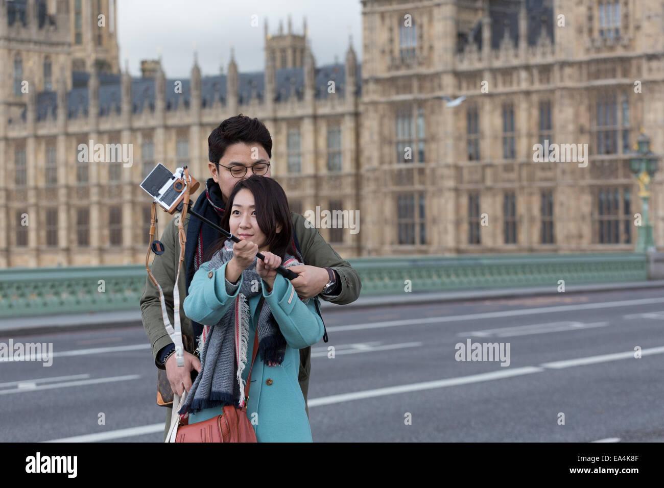 Due turisti cinesi a Londra cattura un selfie fotografia utilizzando una telecamera attaccata a un bastone selfie Immagini Stock