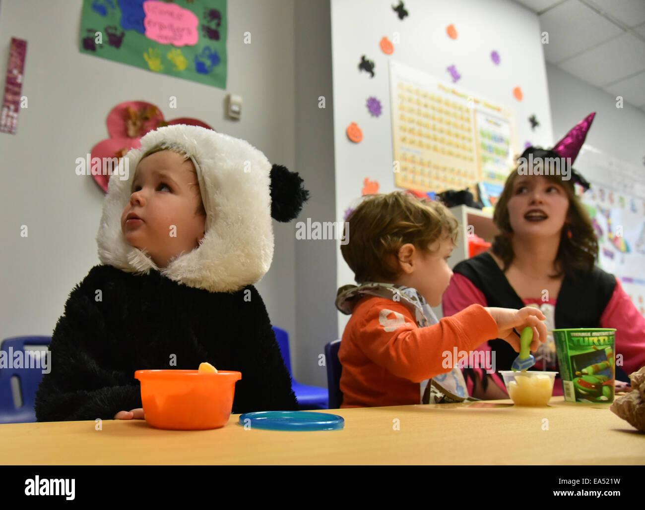 Bambini in età prescolare con il loro insegnante in costume nella loro classe kindergarten di halloween Immagini Stock