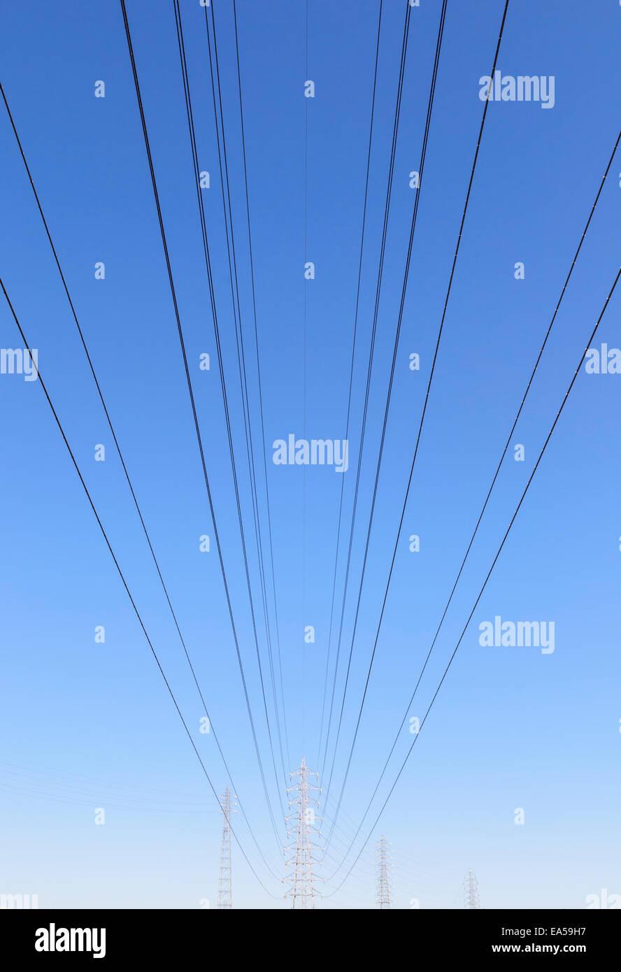 Le linee di alimentazione che portano alle torri di trasmissione a distanza Foto Stock