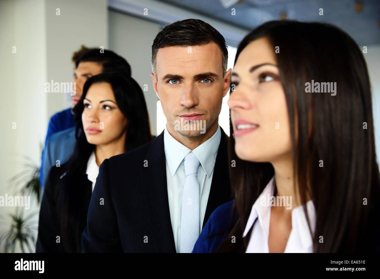 Un gruppo di giovani collaboratori in piedi in una fila in ufficio Immagini Stock