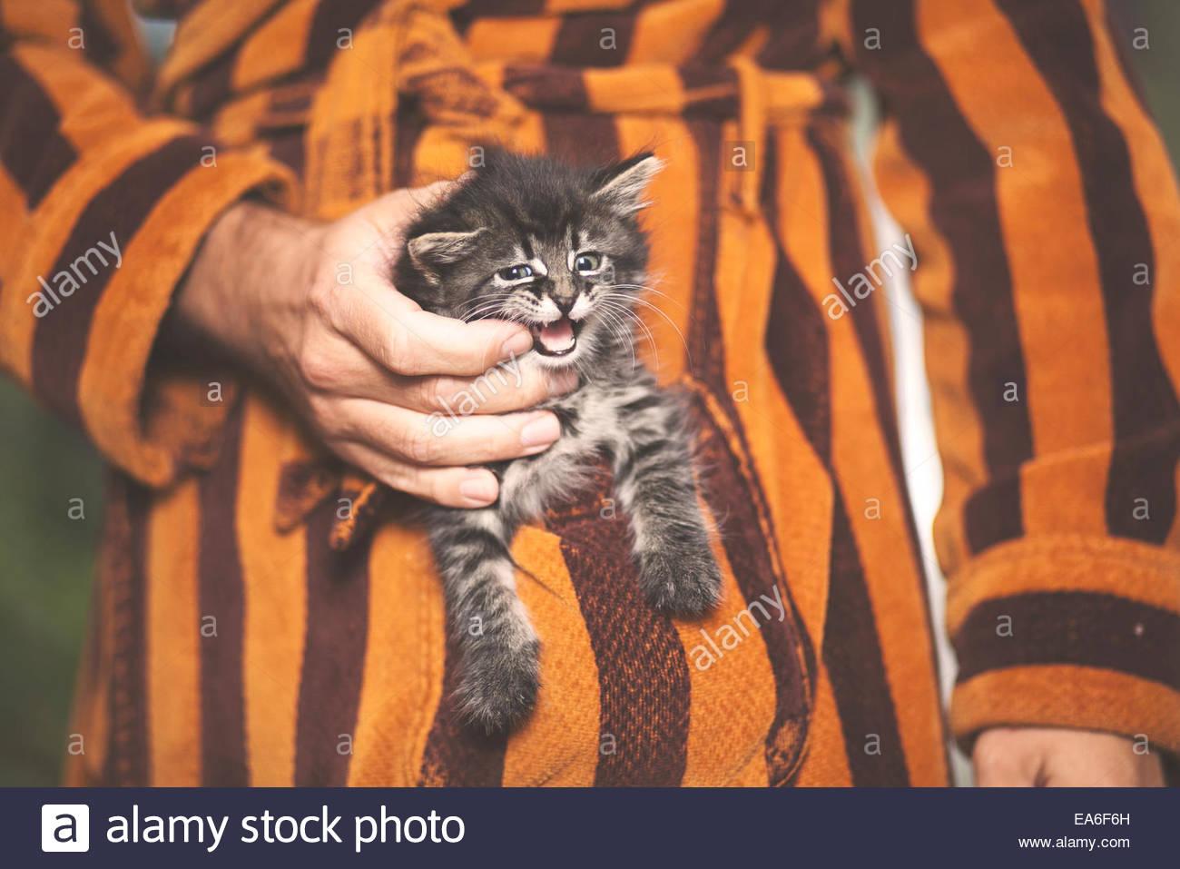 Uomo con un gattino nella tasca del suo accappatoio Immagini Stock