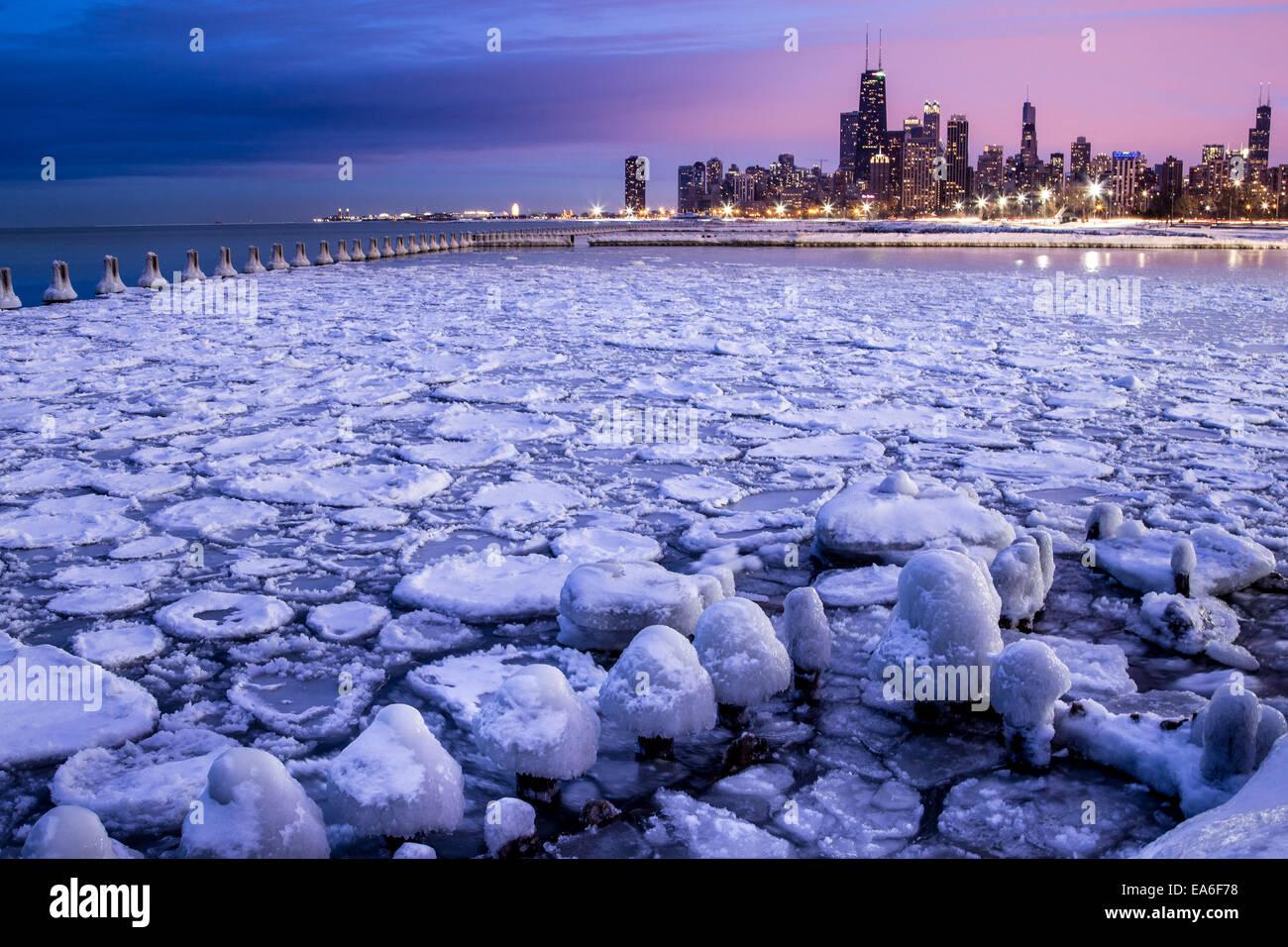 Stati Uniti d'America, Illinois, Chicago, skyline illuminato che si vede attraverso il porto ghiacciato Immagini Stock