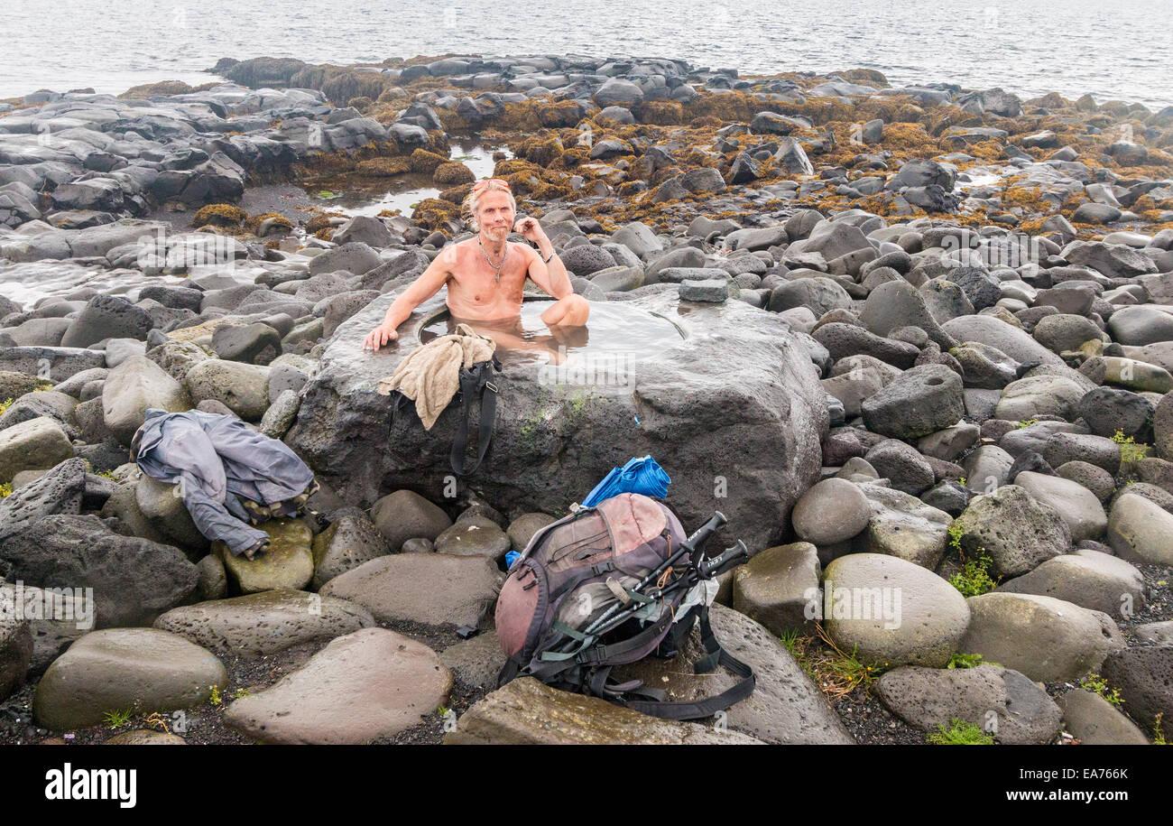 Uomo locale balneazioni in una sorgente calda naturale impostato in rocce presso il litorale di Reykjavik la waterfront. Immagini Stock