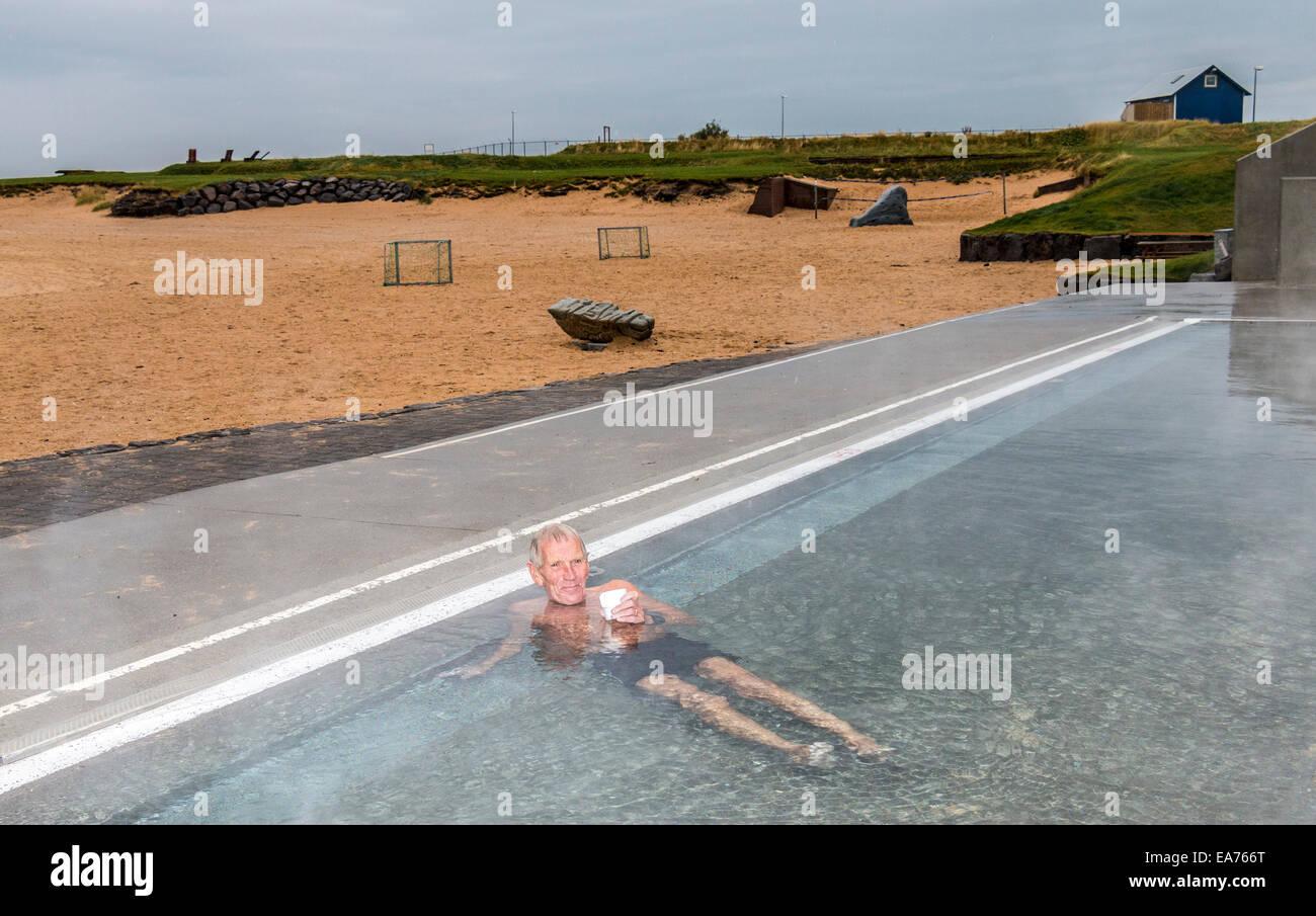 Uomo locale si riscalda se stesso con una tazza di tè in un materiale termicamente piscina riscaldata a Ylstrond, Immagini Stock