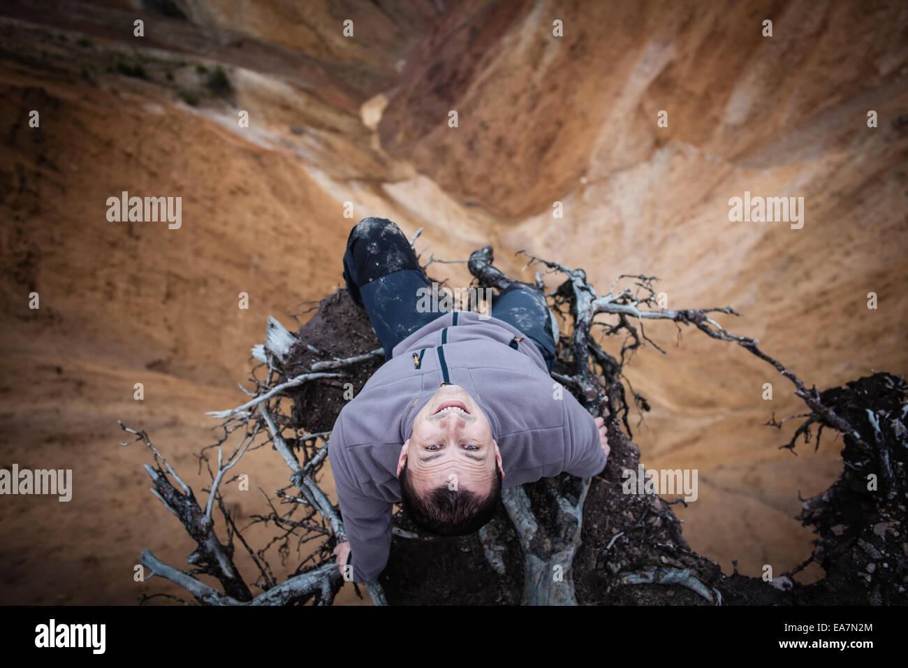 Uomo seduto sul bordo di una scogliera alta, adrenalina, il coraggio e il concetto di rischio Immagini Stock
