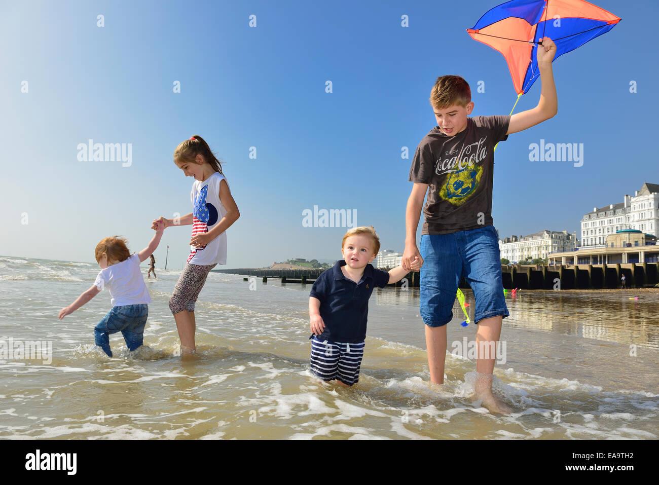 I bambini che corrono lungo la spiaggia con la bassa marea. Eastbourne, East Sussex. Regno Unito Immagini Stock