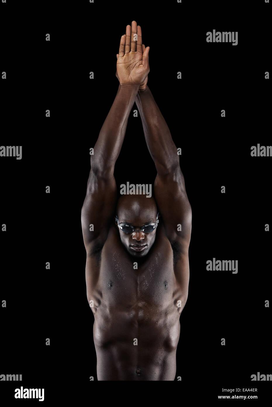 Ritratto di giovane Professional nuotatore con muscolare di costruire attorno a tuffarsi su sfondo nero. Preparazione Immagini Stock