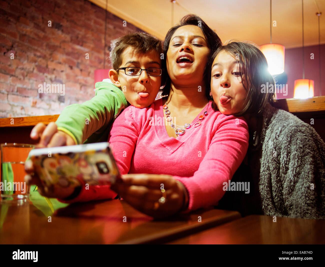 Donna assume selfie sul telefono. Figlia di madre e figlio. Foto Stock
