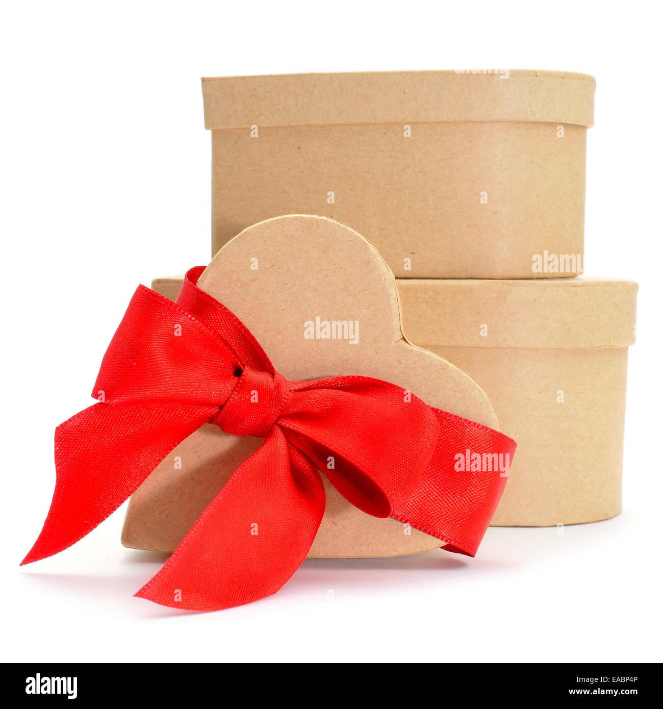 Alcuni a forma di cuore scatole regalo con un nastro rosso su sfondo bianco Immagini Stock