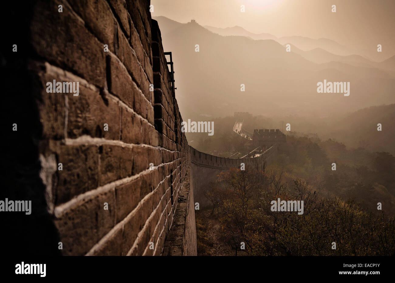 La Grande Muraglia della Cina sorge al tramonto sopra il paesaggio circostante coperto dallo smog presso Badaling, Immagini Stock