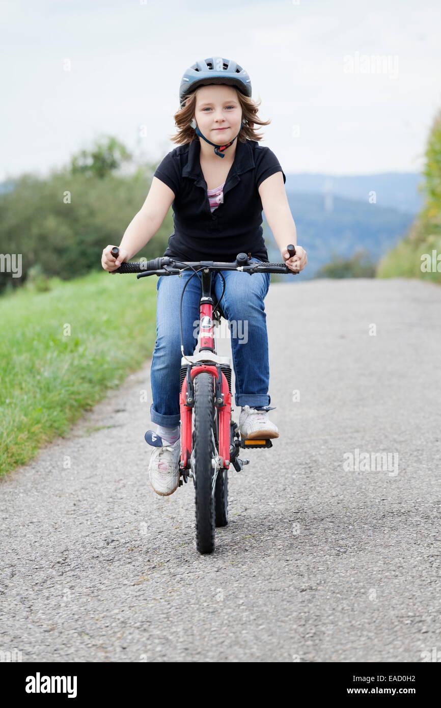 Ragazza 8 anni, in sella ad una bicicletta che indossa un casco Immagini Stock