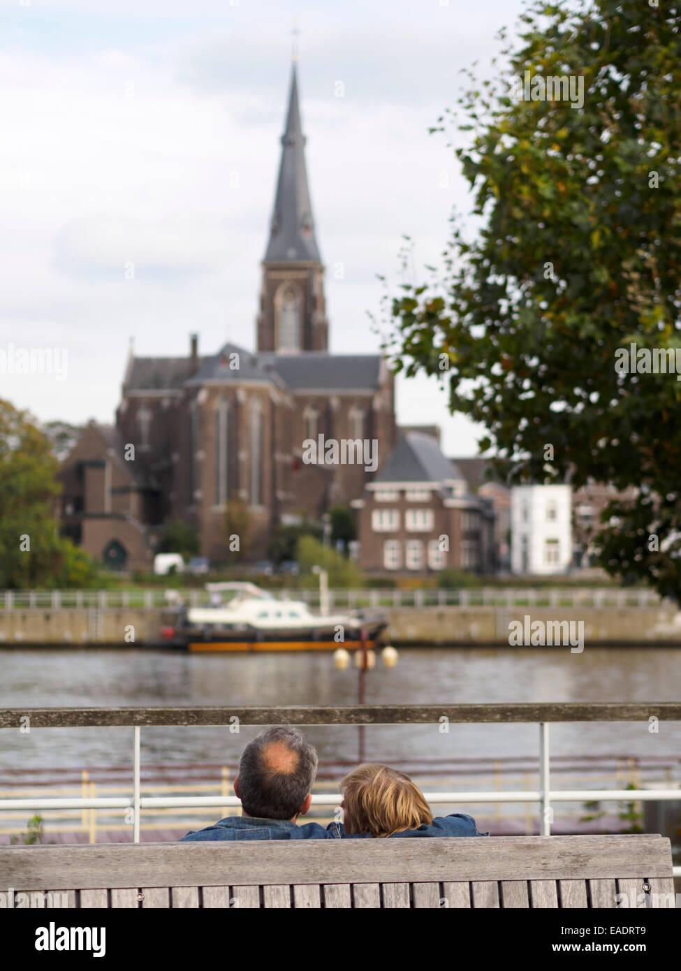 Coppia di mezza età che abbraccia su una panchina nel parco di fronte al fiume Maas e il San Martinus chiesa Immagini Stock