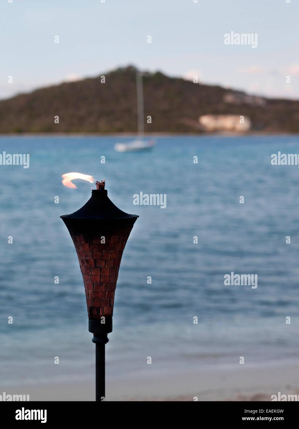 Torcia Tiki al tramonto sulla spiaggia tropicale Immagini Stock