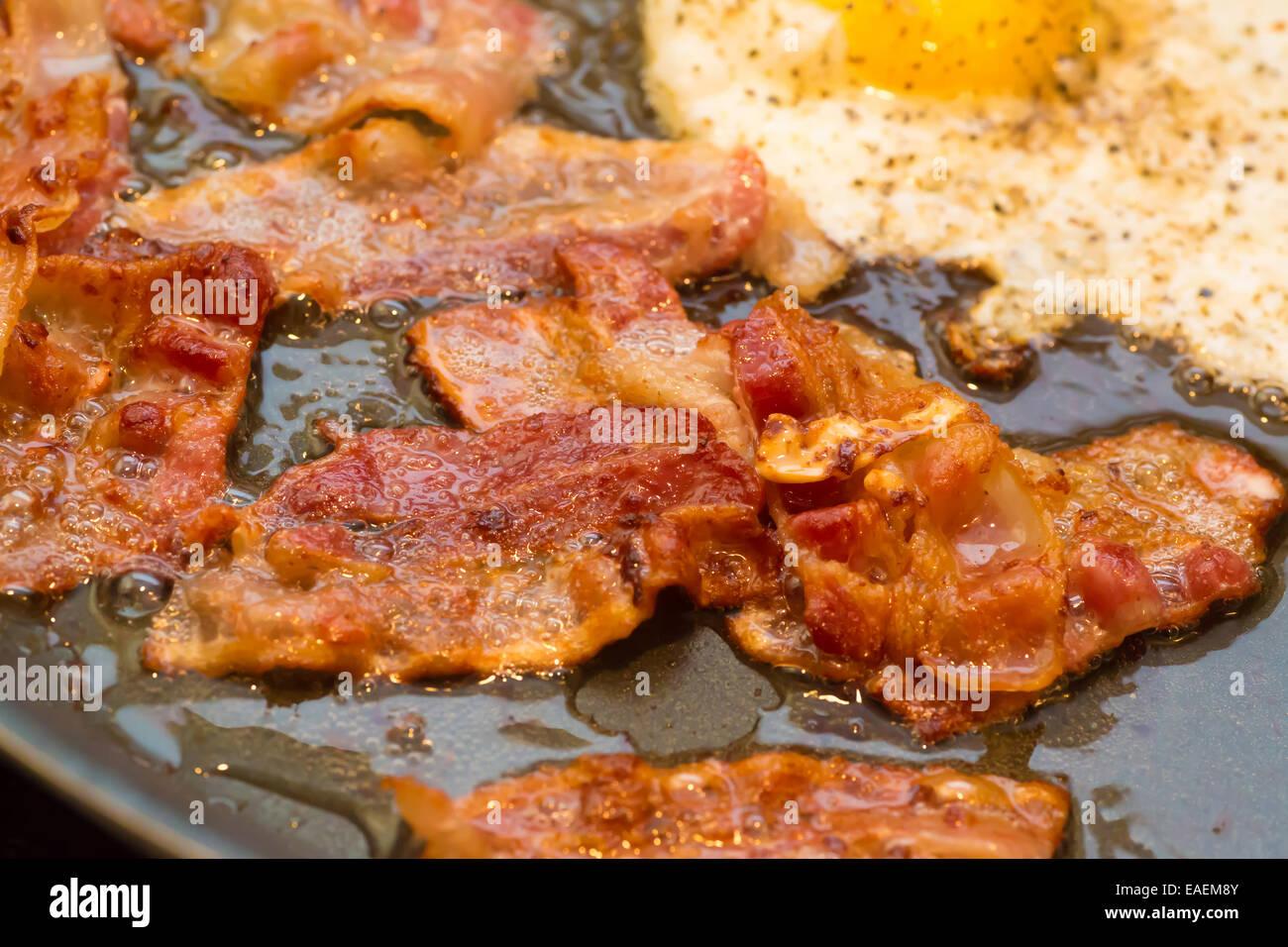 Una colazione grassa della pancetta fritta e un uovo friggere in una padella. Immagini Stock