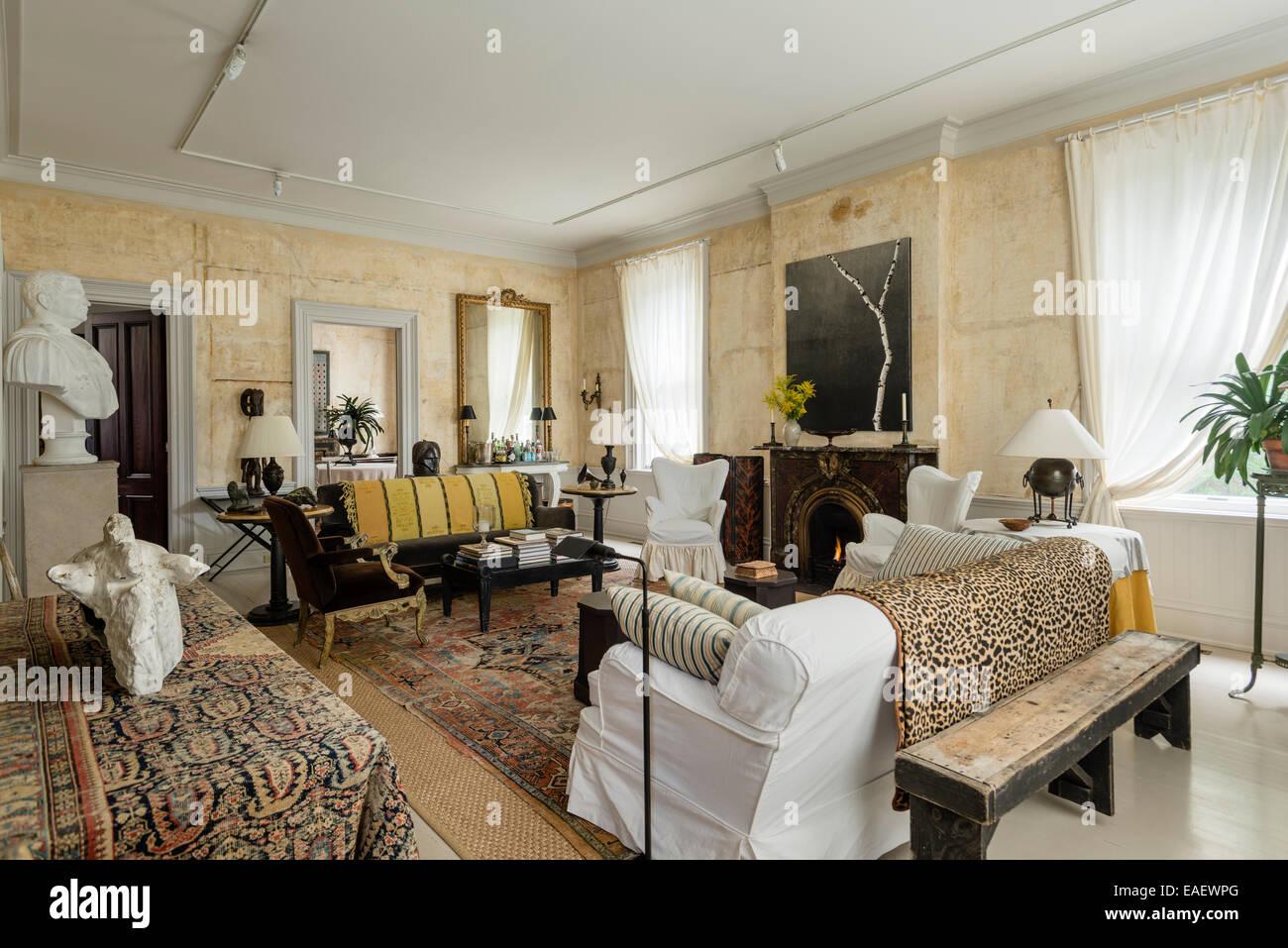 Ampio soggiorno con camino originale e arredate con un mix eclettico di mobili e artwork Immagini Stock