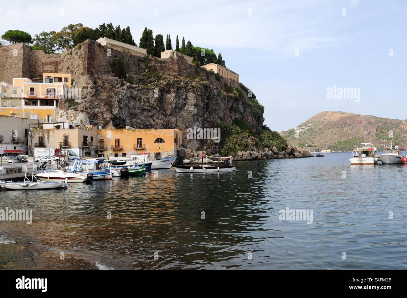 Castello di roccia e piccole imbarcazioni ormeggiate in porto Isola di Lipari Sicilia Italia Immagini Stock