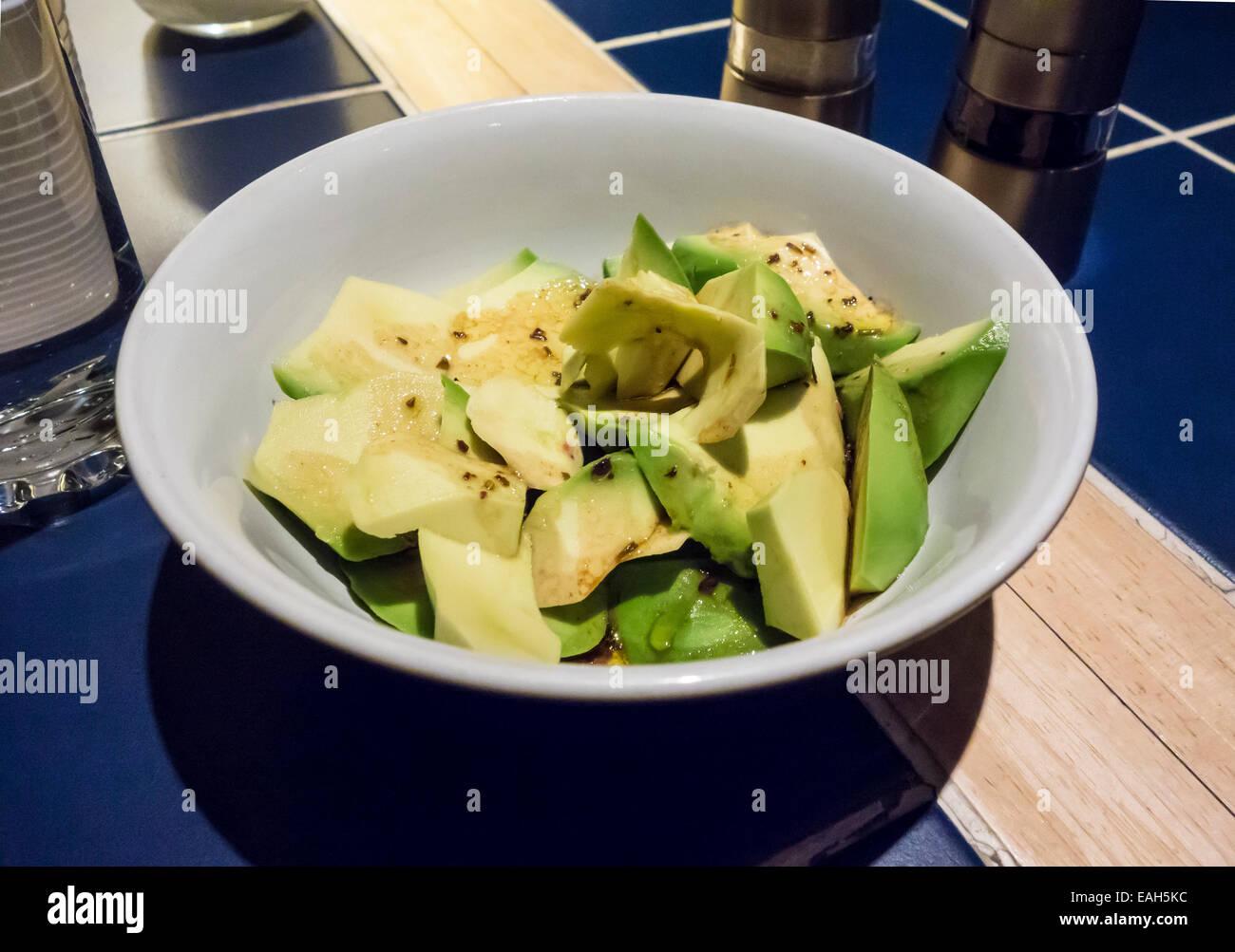 Una ciotola di fette di pere di avocado con medicazione francese Immagini Stock