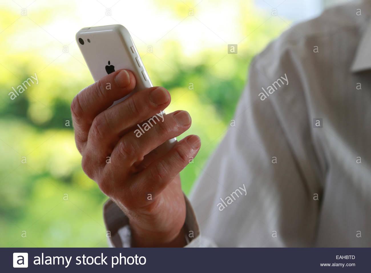 Chiudere shot di man mano che tiene un iphone. Immagini Stock