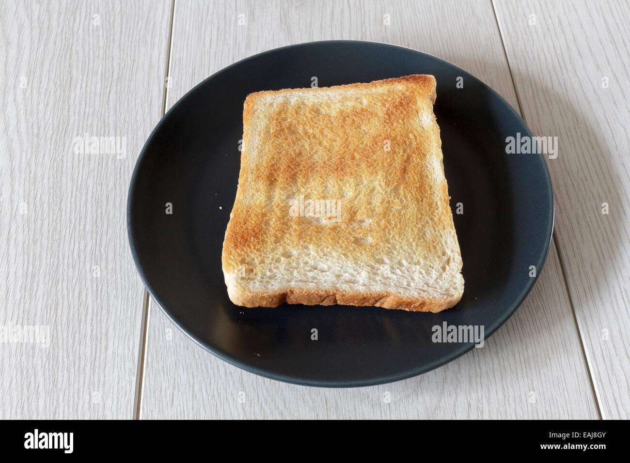 Pezzo di pane tostato a secco su una piastra Immagini Stock