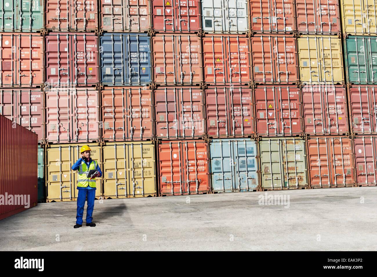 Lavoratore in piedi vicino ai contenitori di carico Immagini Stock