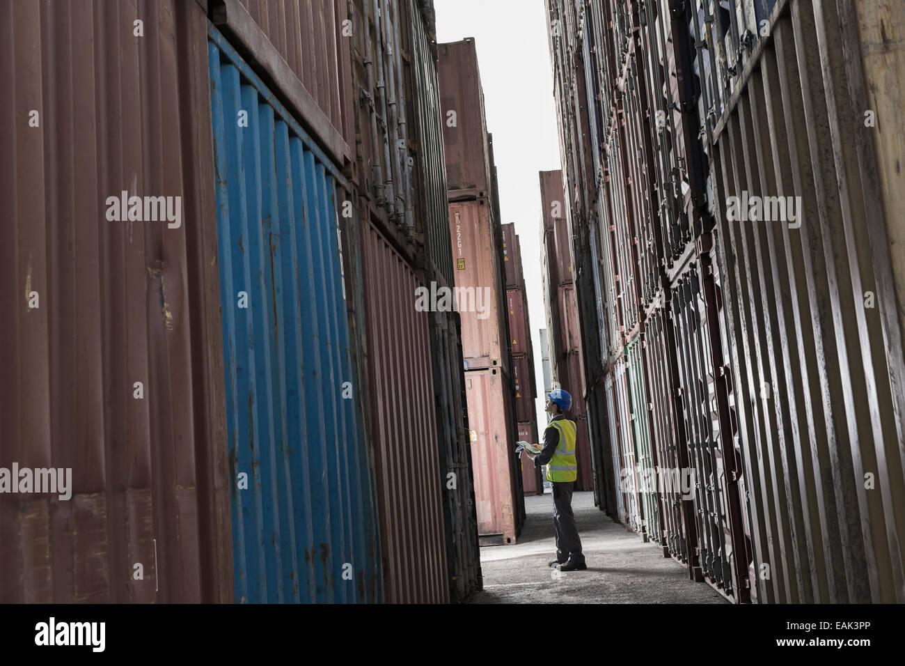 Lavoratore in piedi tra contenitori di carico Immagini Stock